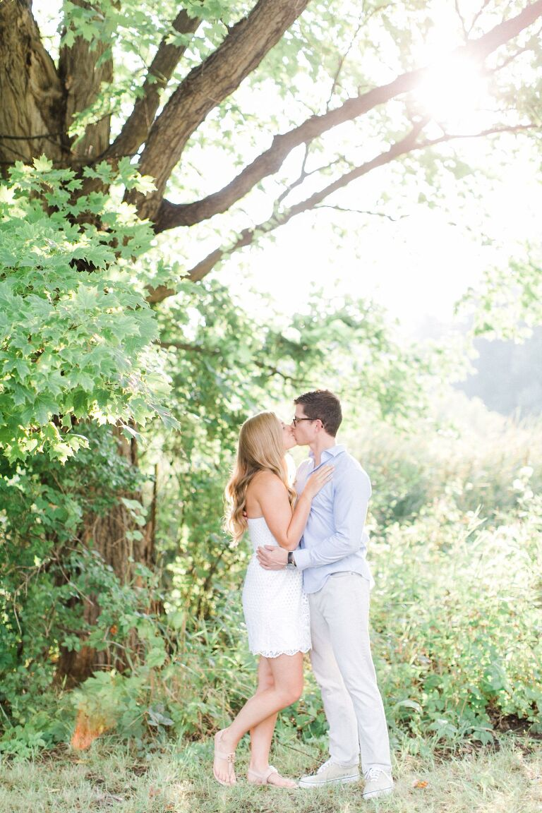 This is an engaged couple kissing under a tree in the summer at The Village at Grand Traverse Commons