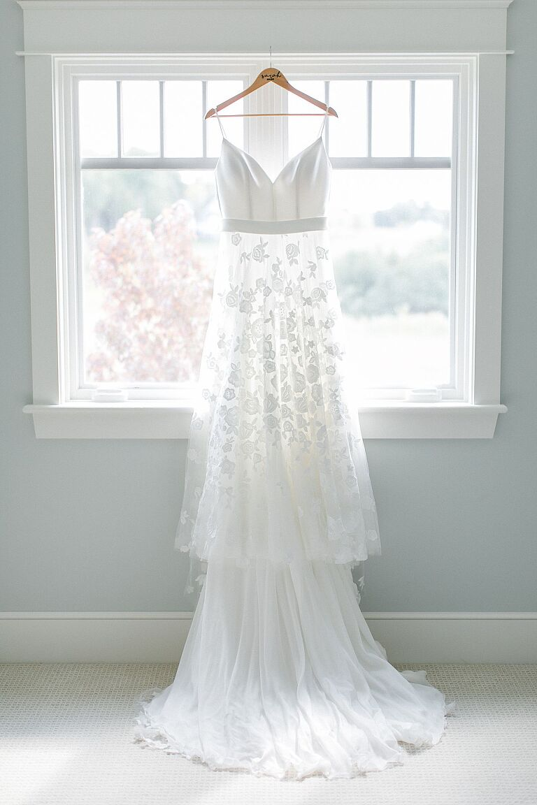 Beautiful lace wedding dress hanging from a window
