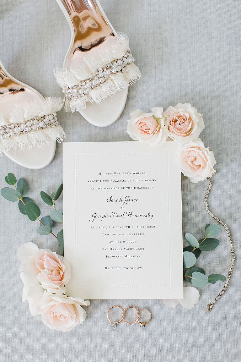 Bridal details including jewelry, invitations, and shoes