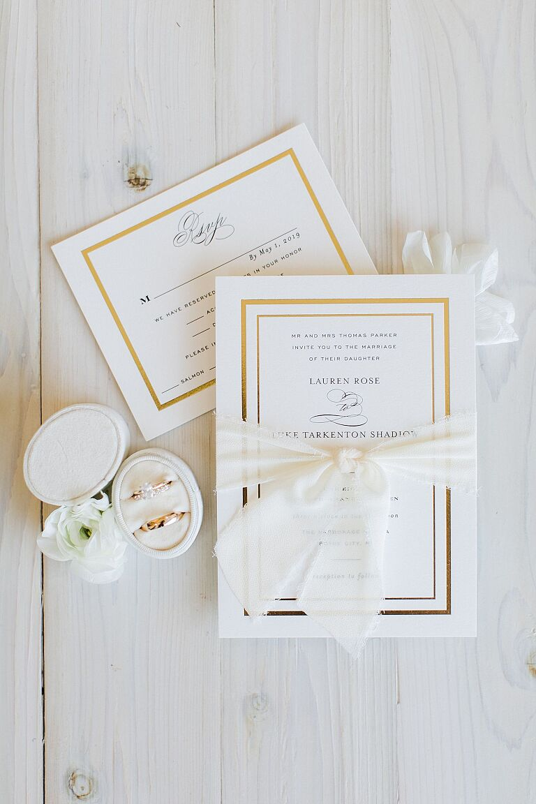 White and gold wedding invitation with a white ribbon tied around it with wedding rings to the side