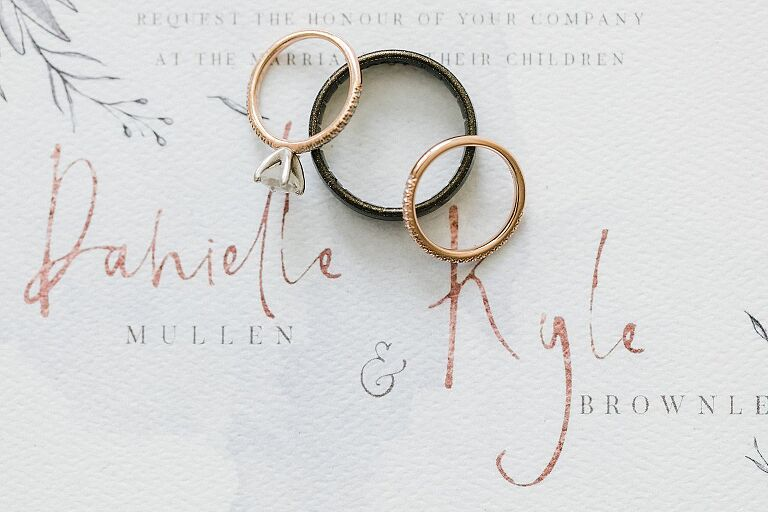 Wedding rings on a white wedding invitation with rose gold accents