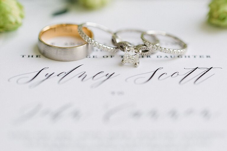 Wedding rings on a white wedding invitation at Aurora Cellars