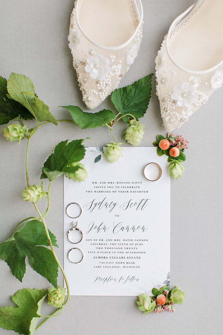 A wedding invitation, white shoes, and rings with hops and flowers around