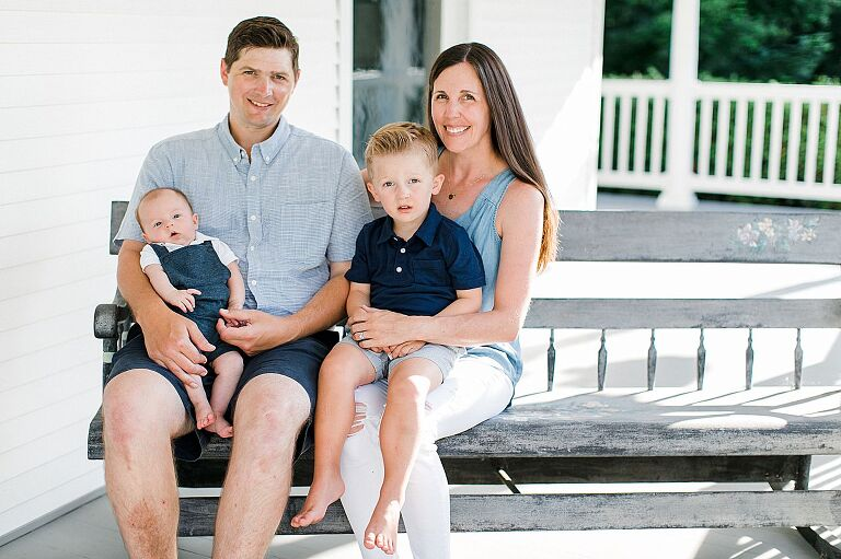A portrait of a family of 4 in Northern Michigan on a white porch