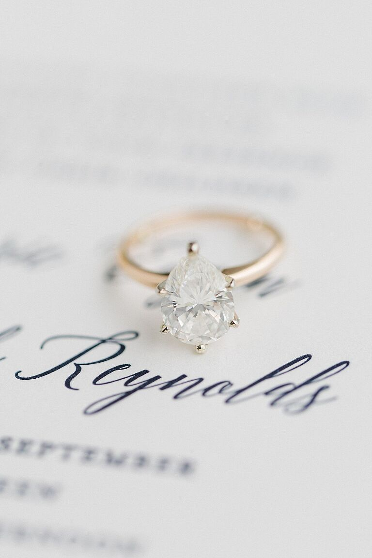 A brides pear shaped engagement ring on a wedding invitation
